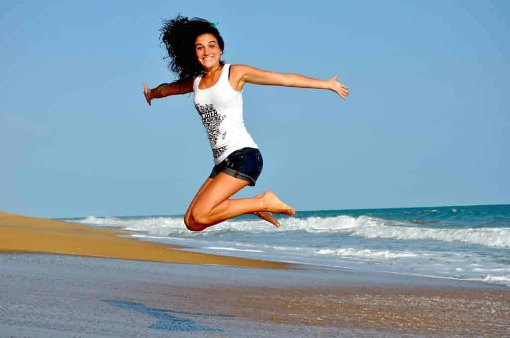 happy-young-woman-jumping-on-beach